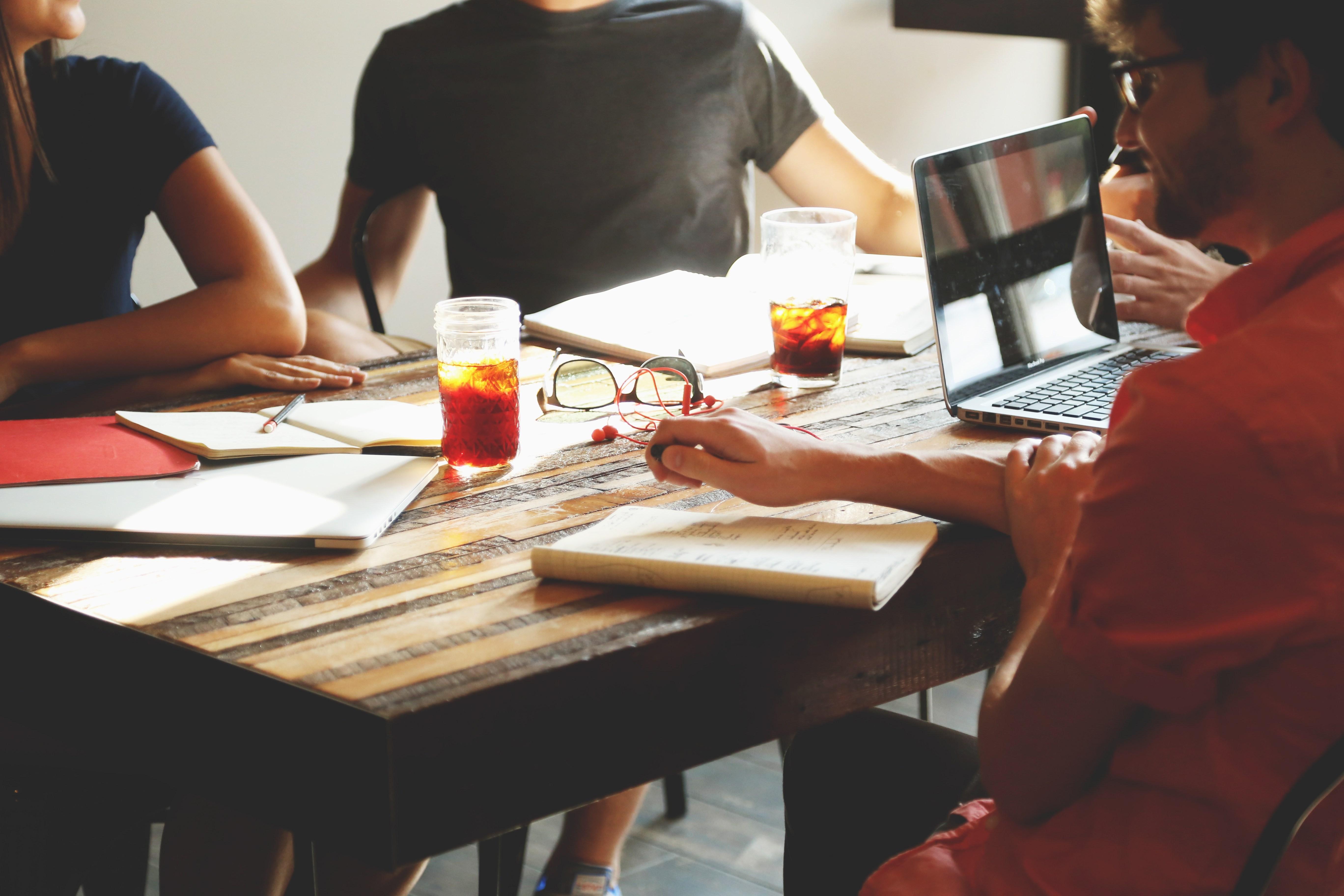bildmotiv-fuer-investoren-start-ups-besprechungstisch-mit-jungen-maennern-an-laptops-und-erfrischungsgetraenken-auf-dem-tisch-thought-leader-systems